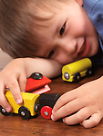 Happy two year old boy playing with a colorful toy train on hardwood floor
