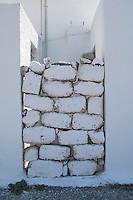 Painted and stacked bricks in a doorway in Greece