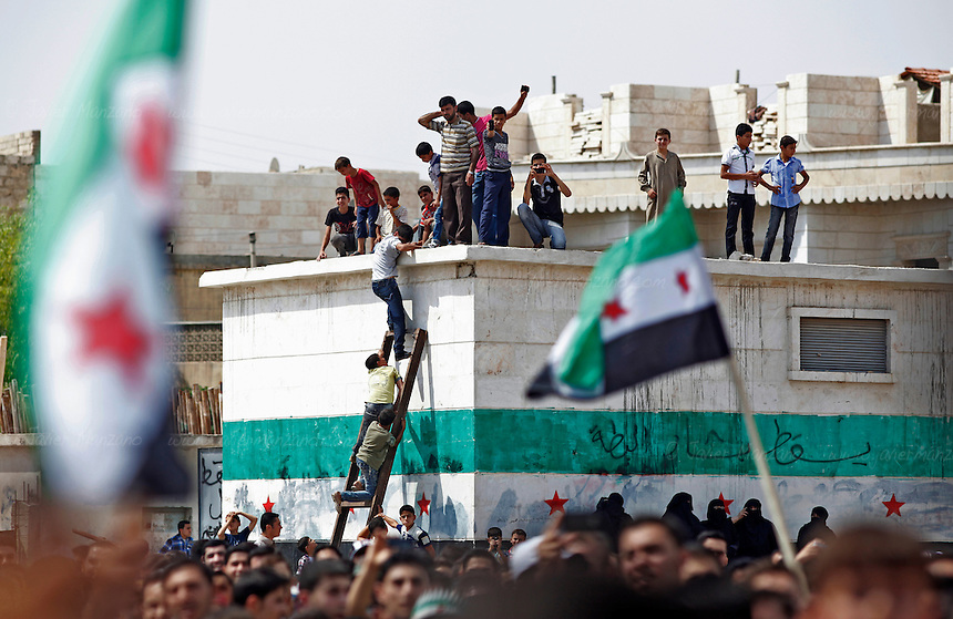 Residents from the northern Syrian town of Al Bab organized a peaceful protest at a main square renamed after the revolution began as &quot;Freedom Square&quot;. More than a thousand people gathered to sing and chant anti-Assad slogans - minutes later, the square emptied as the sound of a fighter jet from the Assad air force began to circle the square. As the people scattered, a blast was heard followed by three other explosions. The fighter jet made at least 6 passes as it fired its 50 caliber  machine gun on the neighborhood below. Doctors at the local underground hospital did not allow this reporter access to the facility because of the load of patients coming in. Unconfirmed reports by the FSA spokesperson in Kilis say that 7 people died and 50 were injured. <br /> <br /> Photo: Javier Manzano / August 31, 2012