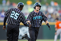 Adam Engel (7) of the Charlotte Knights slaps hands with third base coach Garey Ingram (25) as he rounds the bases after hitting a home run against the Norfolk Tides at BB&T BallPark on May 2, 2017 in Charlotte, North Carolina.  The Knights defeated the Tides 8-3.  (Brian Westerholt/Four Seam Images)