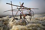 Fishermen remove a giant carp from one of their baskets, at Wagenia Falls, in the middle of the Congo River, DR Congo.