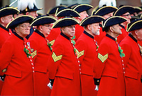 Chelsea Pensioners, wearing their traditional uniform of red coat and black tricorn hat, standing outside the Royal Hospital in Chelsea during the Founder's Day Parade.