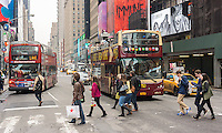 Tour buses at a crosswalk in Times Square in New York on Friday, April 10, 2015. A strong dollar is making it less attractive to visit New York (and spend money!) possibly cutting into the tourism business. The tourism industry generates $60 billion dollars going into the New York economy. 55 million people visited the city last year with tourism jobs jumping 22% in the last decade.  (© Richard B. Levine)