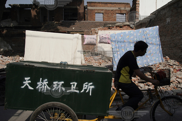 Municipal refuse collector passes a demolished building in a central Hutong (traditional residential area).