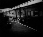 Train station squatter bathes on train platform, West Bengal, India.
