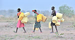 Girls in Yei, Southern Sudan, walk to a well to get water.