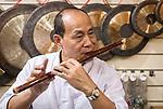 Music store owner in Shanghai, China plays Dizi Chinese flute
