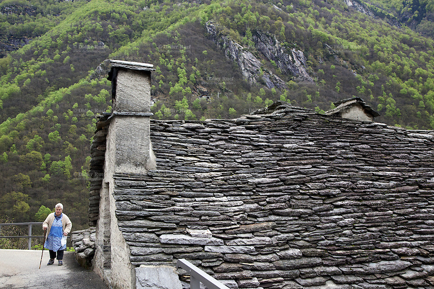Switzerland. Canton Ticino. Corippo lies in the Verzasca valley. Clarina Scettrini walks on the concrete road. The  houses are built from the local Ticino granite with stone roofs and have changed little for several hundred years. Clarina Scettrini is a member of the town council consisting of three local citizens. A town council is a democratically elected form of government for small municipalities. A council may serve as both the representative and executive branch. With a population of just 16, Corippo is the smallest municipality in Switzerland. Despite this, it possesses the trappings of communities many times its size such as its own coat of arms. The village has maintained its status as an independent entity since its incorporation in 1822. 8.05.13 © 2013 Didier Ruef