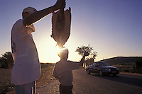 Father and son sell food ( armadillo and peanut ) to drivers at road in countryside Rio Grande do Norte State, northeastern Brazil.