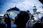 Acehnese watch birds flock to the Grand Mosque near the Aceh Market, in Banda Aceh, Indonesia, on Sunday, Dec. 12, 2010.