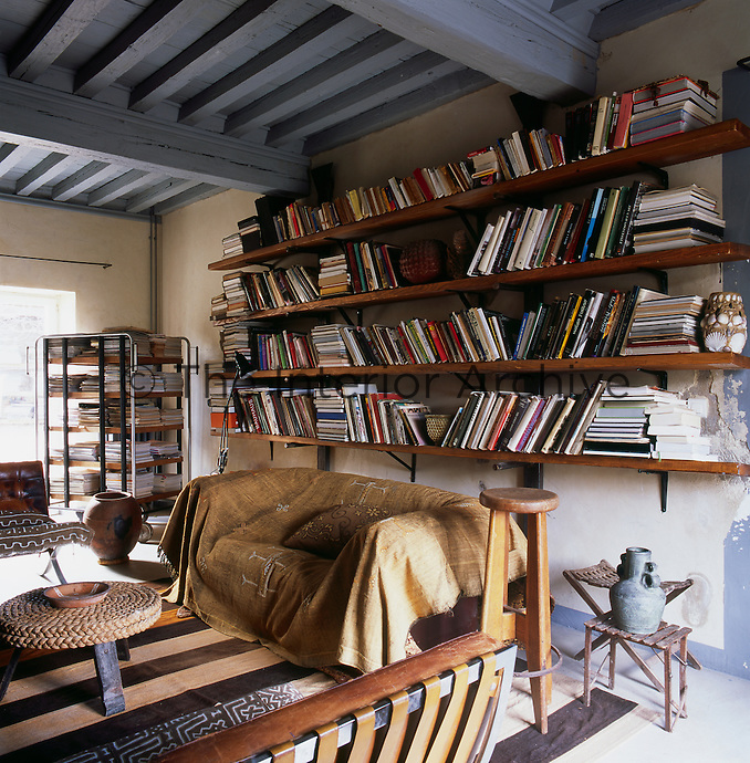 An informal home library. The room has a grey painted beamed ceiling and stone walls. Books are arranged on wall-mounted shelves on one wall and in an old postal sorting cart. A sofa draped with a fabric throw.