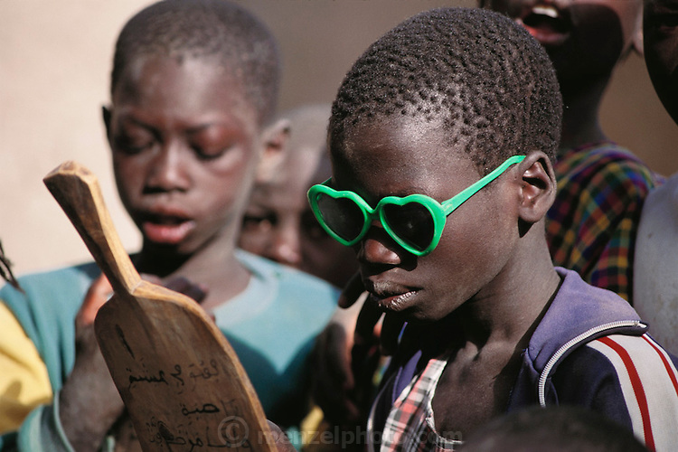 """This young boy with green heart-shaped sunglasses is reading Koranic verses on a wooden tablet under the watchful eye of the Imam of Kouakourou village in Mali as he teaches a Koranic lesson to students. Several of Soumana Natomo's children attend these classes, along with classes at what they call, """"the modern school"""" taught in French, where they learn math and reading. Material World Project."""