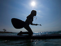 A young girl learns how to standup paddleboard at Mahai'ula Beach (part of Kekaha Kai State Park), Big Island.