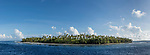 Apataki Atoll, Tuamotu Archipelago, French Polynesia; a panoramic view of  the palm tree covered island bordering one side of Tehere Pass from inside the channel on Apataki Atoll