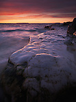 Colorful sunset nature landscape scenery of Georgian Bay rocky shore under red sky. Bruce Peninsula National Park, Ontario, Canada.