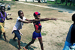 KINSHASA, DEMOCRATIC REPUBLIC OF CONGO - JULY 4: Esther Yandakwa (c), age 9, plays a game with her friends at a yearly summer camp run by Orper, a local NGO on July 4, 2006 in N Djili outside Kinshasa, Congo, DRC. The NGO has several shelters for homeless boys and girls in Kinshasa and has a program that reunites children with their families. The capital has a growing problem with children displaced by war, poverty and many has been rejected by their families and forced on the streets. About 15,000 children are estimated to live on the streets of Kinshasa. About fifty girls got to spend a week relaxing, playing, swimming eating three meals a day. Most important of all, it took them off the hard streets of Kinshasa, where they are often abused, take drugs and forced into prostitution. Esther has lived on the streets for a few years and run away from her family. She abuse drugs, alcohol and works as prostitute. Congo, DRC is in ruins after forty years of mismanagement by the corrupt dictator and former president Mobuto Sese Seko. He fled the country in 1997 and a civil war started. The country is planning to hold general elections by July 2006, the first democratic elections in forty years. (Photo by Per-Anders Pettersson)