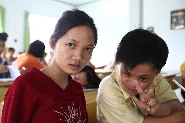 A girl who cannot hear or speak looks shyly at the camera while her friend flashes the peace sign at a center for children who have been affected by dioxin exposure in the village of Hoa Nhon, near Da Nang, Vietnam.  The Da Nang Association of Victims of Agent Orange/Dioxin says that more than 1,400 children around the city suffer from mental and physical disabilities because of dioxin exposure, a legacy of the U.S. military's use of Agent Orange and other herbicides during the Vietnam War more than 40 years ago. About 60 children attend the Hoa Nhon center each day. Many of them have mental disabilities or they cannot hear or speak. Children are taught to read and write, sew clothes. make handicrafts and help their families raise crops and livestock. Children who cannot hear or speak are taught sign language. The Vietnam Red Cross estimates that 3 million Vietnamese suffer from illnesses related to dioxin exposure, including at least 150,000 people born with severe birth defects since the end of the war. The U.S. government is paying to clean up dioxin-contaminated soil at the Da Nang airport, which served as a major U.S. base during the conflict. But the U.S. government still denies that dioxin is to blame for widespread health problems in Vietnam and has never provided any money specifically to help the country's Agent Orange victims. May 29, 2012.