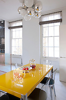 "A bright yellow lacquer table and Murano ""Vanity"" chairs in the breakfast area are situated beneath a pendant light by Emmanuel Babled in this light kitchen"