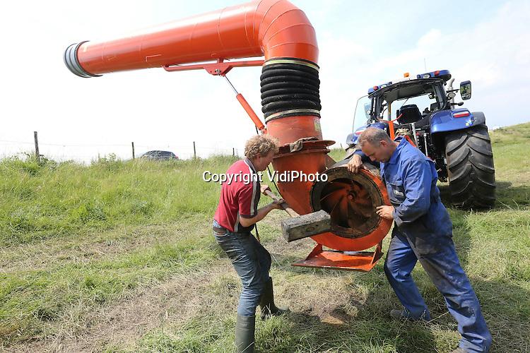Foto: VidiPhoto<br /> <br /> OCHTEND - Opnieuw stijgt het water in de rivieren en tot overmaat van ramp gaat de enorme waterpomp die de polder tussen Ochten en Dodewaard droog moet maken, ook nog eens stuk. Melkveehouder Jan-Willem van Rooijen uit Dodewaard en loonbedrijf Van der Woerd uit Zoelen proberen koortsachtig het gevaarte dinsdag weer aan de gang te krijgen. Het is tot nog toe gelukt om het kwelwater in het gebied een halve meter te laten zakken, waardoor een deel van de gewassen gered kan worden. Zo'n 10 ha. aan (suiker)bieten, ma&iuml;s moet echter als verloren worden beschouwd. De polder is zo'n 400 ha. groot. Naast grasland en natuur staat er zo'n 200 ha. aan gewassen. De enorme installatie pompt zo'n 4000 kubieke meter water per uur uit de polder en is eigendom van Van Rooijen en Van der Woerd. Het water in de Waal staat al vier weken boven de 12 meter. Zo'n lange periode met hoogwater in deze tijd van het jaar is nog niet eerder voorgekomen.