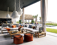 "With its Tiki hut, ocean views and Indonesian-made furnishings, a ""South Seas"" breeze seems to linger near the loggia of this 18,400-square-foot, Vero Beach Bauhaus-style home, where Sunbrella covers custom sofas beneath bamboo pendants from Roost. Along with the exotic textures and organic accessories, a pizza oven is a prime source of pleasure."
