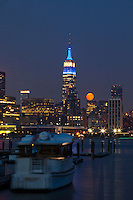A full moon rises next to the Empire State Building in New York City seen from Hoboken in New Jersey,  Aug 21, 2013. Photo by Eduardo Munoz Alvarez / VIEWpress.