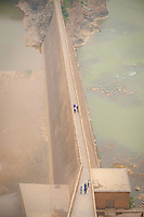 Daytime vertical view from the Sānménxiá Dam of people on a walkway on the Huang He and smokestacks at a power plant facility in the Sānménxiá Shì Húbīn District in Hénán Province.  © LAN