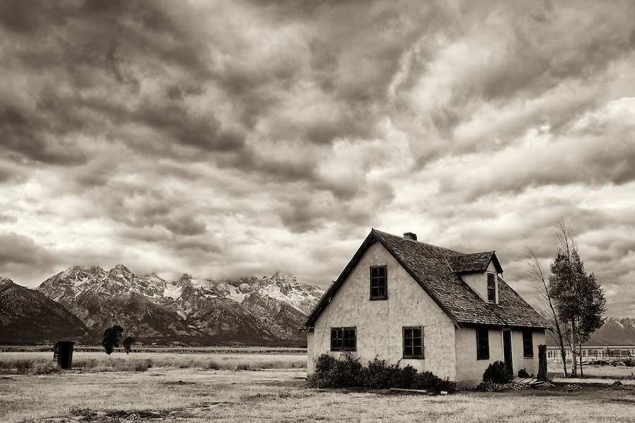 Dramatic clouds sail over an old house in the Mormon Row area of Grand Teton National Park, Wyoming.