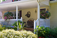 Front porch garden, hanging baskets of annual flowers, firewood holder, front door, shutters on windows, white railing, Hakonechloa hakon ornamental grass, hydrangea, climbing clematis vine,
