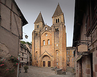 West facade of the Abbatiale Sainte-Foy de Conques or Abbey-church of Saint-Foy, Conques, Aveyron, Midi-Pyrenees, France, a Romanesque abbey church begun 1050 under abbot Odolric to house the remains of St Foy, a 4th century female martyr. An arched portico surrounds the doors, above which is a carved tympanum. The church is on the pilgrimage route to Santiago da Compostela, and is listed as a historic monument and a UNESCO World Heritage Site. Picture by Manuel Cohen