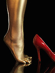 Woman bare legs covered with gold and red high heel shoes. Isolated on black background.
