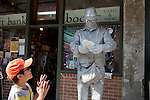 "A boy is surprised as ""Silver Man"" comes to life and starts to eat the boy's sandwich after taking it. Pike Place Market, Seattle."