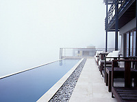 Long infinity pool with a misty sea view - pebbles and sandstone paving pebbles with seating along the porch