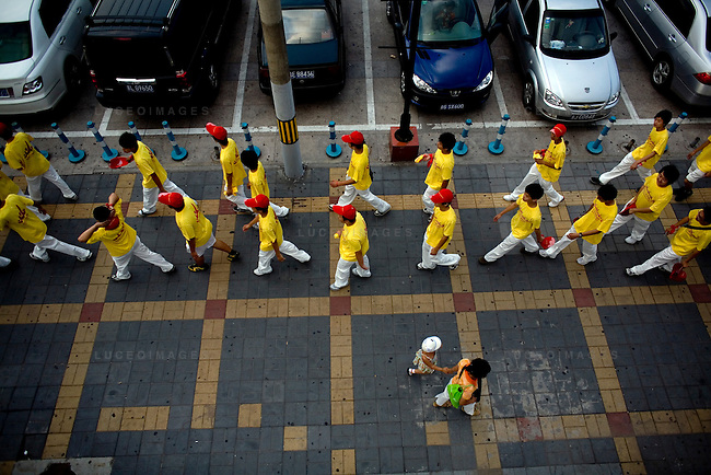 Cheer Beijing Workers walk towards Worker's Stadium for the USA vs Japan women's soccer match in Beijing, China on Monday, August 18, 2008.  The Cheer Beijing Workers are asked to fill the empty seats and cheer for China at live televised venues. Kevin German