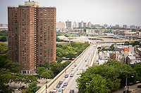 Looking east on West 155th Street towards the Macombs Dam Bridge into the Bronx, from Harlem in New York seen on Sunday, July 13, 2014.  One of the buildings of the massive NYCHA Polo Grounds Houses complex of apartments is on the right.  (© Richard B. Levine)