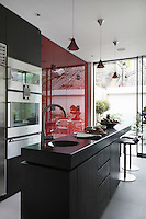 The bright contemporary kitchen connects through sliding plate glass windows to a small patio beyond