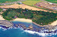 Great  aerial shot of secluded Lanikuhonua cove on the leeward coast of Oahu showing the surf gently skimming the coral reef and empty white sand crescent beach with  lush green foliage surrounding it.