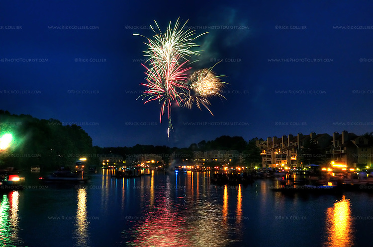 US Independence Day Fireworks over Lake Thoreau, Reston, Virginia.  As dark falls, everyone who has a boat or floating dock embarks to enjoy the show as lakeside residents treat one another to a spectacular impromptu fireworks show over the lake.  &copy; Rick Collier.