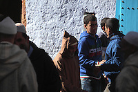 People on a street in the medina or old town of Chefchaouen, including an old man wearing a djellaba and young boys in modern clothes, in the Rif mountains of North West Morocco. Chefchaouen was founded in 1471 by Moulay Ali Ben Moussa Ben Rashid El Alami to house the muslims expelled from Andalusia. It is famous for its blue painted houses, originated by the Jewish community, and is listed by UNESCO under the Intangible Cultural Heritage of Humanity. Picture by Manuel Cohen