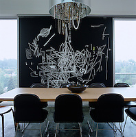 An eclectic chandelier made out of necklaces hangs over the dining room table positioned infront of a large abstract black and white artwork