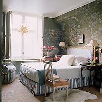 In the master bedroom an 18th century French chair has an ostrich-covered seat and the custom-made De Gournay wallpaper is embellished with splashes of gold leaf and resin by the artist Nancy Lorenz