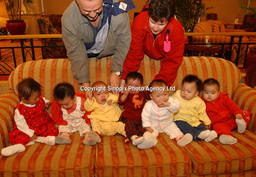 Newly adopted Chinese female babies line-up on sofas for a group photograph. The babies belong will soon make their way to new homes in the west.