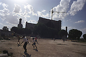 Children play football in front of the Bibi-Khanym Mosque, one of the Islamic world's largest mosques. Having collapsed in an earthquake in 1897 it is now being restored under the patronage of UNESCO. Uzbekistan