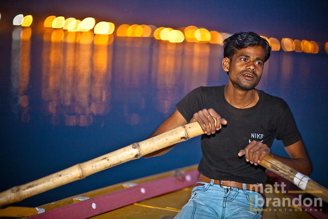 A young man rows a boat along the Ganges River early in the morning. The city of Varanasi, India is in the background