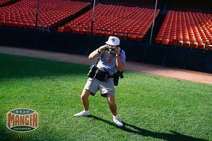 SAN FRANCISCO, CA - Bay Area press photographer Eric Risberg poses for a picture at home plate with his Widelux camera before the San Francisco Giants game against the Cincinnati Reds at Candlestick Park in San Francisco, California on September 27, 1992. (Photo by Brad Mangin)