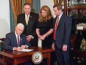 United States Vice President Mike Pence, left, signs the affidavit of appointment after US Representative Mike Pompeo (Republican of Kansas), left center, was sworn-in as Director of the Central Intelligence Agency (CIA) in the Vice President's ceremonial Office at the White House in Washington, DC on Monday, January 23, 2017.  Pompeo was accompanied by his wife, Susan, right center, and his son, Nick, right.<br /> Credit: Ron Sachs / Pool via CNP