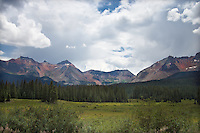 Colorful San Juan Mountains with green field and trees in foreground. Mountains are colorful with minerals