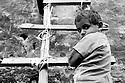 A little boy standing on a ladder in the French colony slum in the city center of Islamabad.
