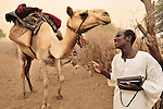 An Arab man, with his camel, listening to news on the radio. Many Arabs in Darfur have grown weary of the alliance with the government, and several Arab militia leaders have broken from the government.