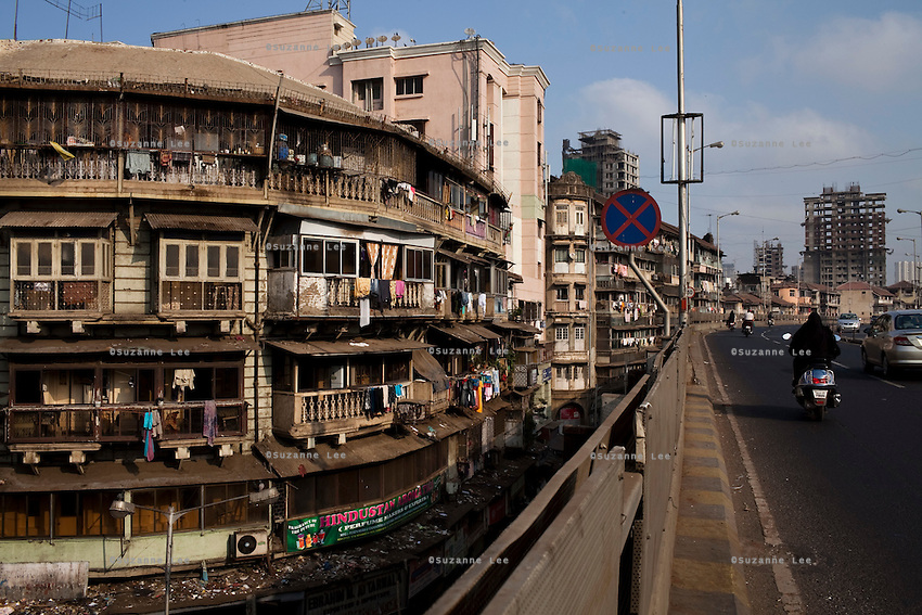 A flyover road next to a chawl (tenements) in Mumbai, India. Photo by Suzanne Lee