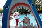 SOUTHBURY, CT--- -073115JS06--Through a cardboard cutout of a shark, lifeguards Brendon Hessler left, and Steve Pendergast watch the kids as they swim during the Nautical Night pool party at the Southbury town pool at Ballantine Park in Southbury. More than 150 middle school age kids showed up for swimming, games and food. The pool will host a Family Movie Night on Monday with events starting at 5:30 and the movie Frozen being shown at around 7:30.  <br />  Jim Shannon Republican-American